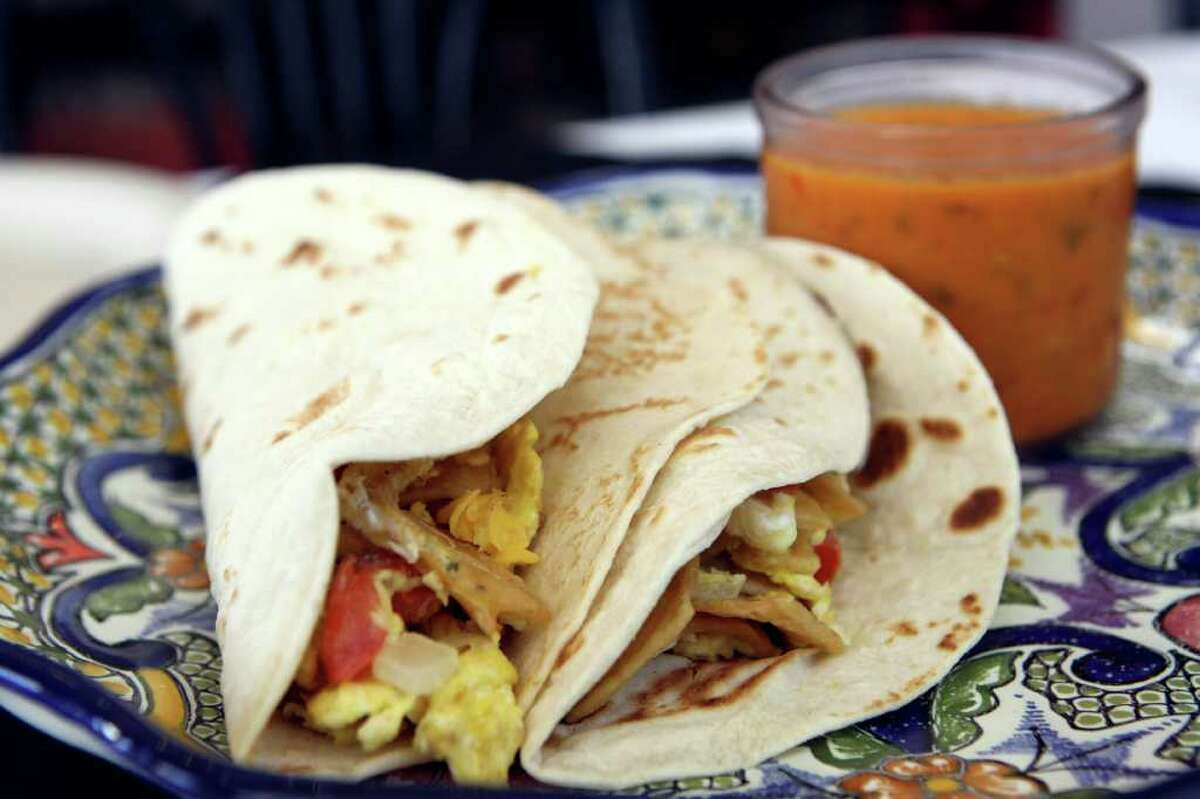 """Breakfast tacosWhere: Café Salsita, 555 E. Basse Road, Suite 113, 210-826-6661Why we love it: Whether you choose a tender flour tortilla or an earthy corn tortilla, or opt for potato and egg, bean and cheese or machacado filling, you'll love Café Salsita's plump breakfast tacos, especially when you top them with one of two salsas, a spunky red or the gourmet chile de arbol, a rich, creamy, orange salsa that's flecked with bits of fresh onion and cilantro. We order them so often that we've been asked, """"The usual?"""" when we call.Cost: $1.50-3.25, depending on filling"""