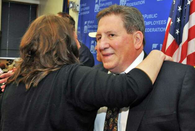 PEF vice president Tom Comanzo, at right, gets a hug from union member Susan Olsen, whose job was saved by the results of the final count of re-vote accepting the PEF contract during a news conference at PEF headquarters in Colonie Thursday Nov. 3, 2011.   (John Carl D'Annibale / Times Union) Photo: John Carl D'Annibale / 00015258A