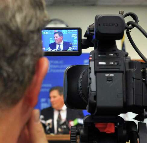 TV cameras record PEF vice president Tom Comanzo as he announces the results of the final count of re-vote accepting the PEF contract during a news conference at PEF headquarters in Colonie Thursday Nov. 3, 2011.   (John Carl D'Annibale / Times Union) Photo: John Carl D'Annibale / 00015258A