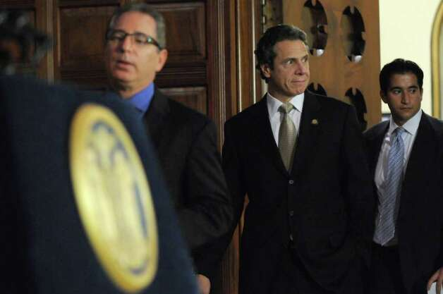 Gov. Andrew Cuomo walks into the Red Room from his office to discuss PEF workers voting in favor of the state's contract proposal, thereby avoiding layoffs, in the Capitol on Thursday  Nov. 3, 2011 in Albany, NY.  Director of Operations Howard Glaser is at left, and spokesman Josh Vlasto is at right.  (Philip Kamrass / Times Union ) Photo: Philip Kamrass / 00015277A