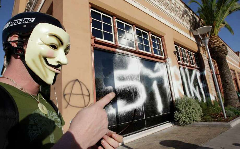 A demonstrator looks at the graffiti left by demonstrators at a Whole Foods market in Oakland, Calif., Wednesday, Nov. 2, 2011 during an Occupy protest. Protestors escalated their tactics beyond marches, rallies and tent camps Wednesday and moved to disrupt the flow of goods at the nation's fifth-busiest port. (AP Photo/Paul Sakuma) Photo: Paul Sakuma / AP