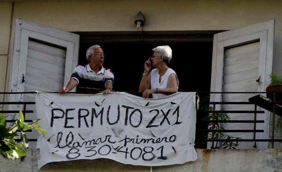 "FRANKLIN REYES: ASSOCIATED PRESS HOMEOWNERS: Nilda Bouzo speaks with her husband Ives Lopez next to a sign that reads in Spanish ""Exchange Apartment Two for One"" on their home balcony in Havana. Property exchanges and signs such as this one were already legal in Cuba. Photo: Franklin Reyes / AP"