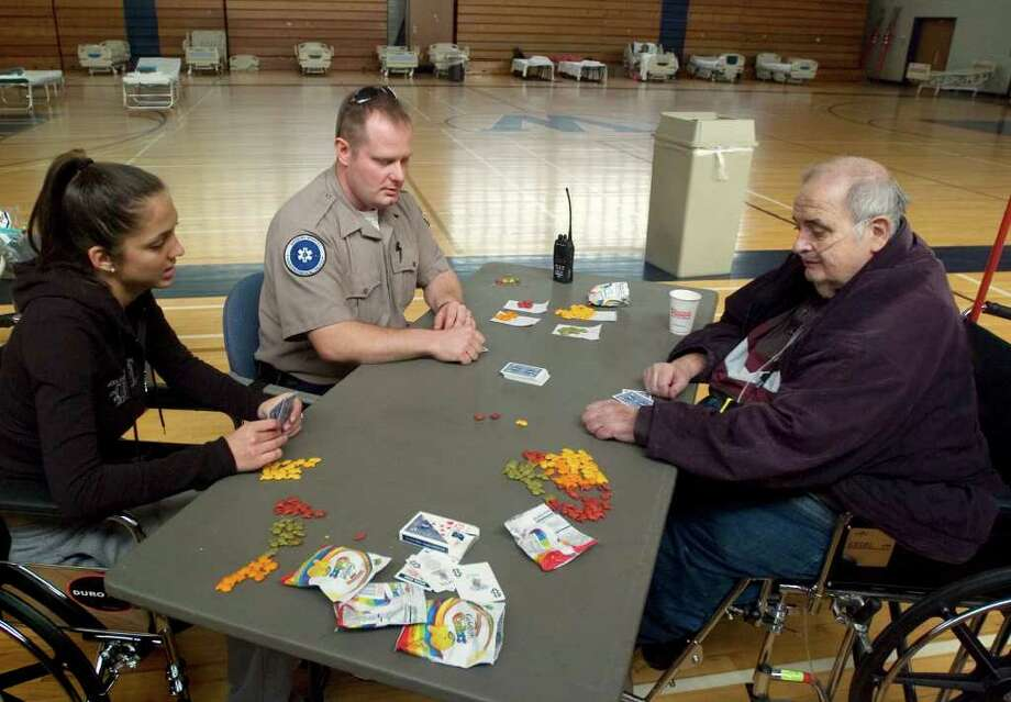 Taylor Iodice, left, a nursing student at Western Connecticut State University, and Tim Lewis, an EMT with Danbury Hospital, play Texas Hold 'em with Bill McDonough, of Newtown, at the functional needs shelter set up at Bill Williams Gymnasium at Western Connecticut State University in Danbury on Thursday, Nov. 3, 2011. The shelter was set up for at-risk people who were discharged from a hospital and/or require constant medical care. McDonough was at the shelter because of his constant need for oxygen. Photo: Jason Rearick / The News-Times