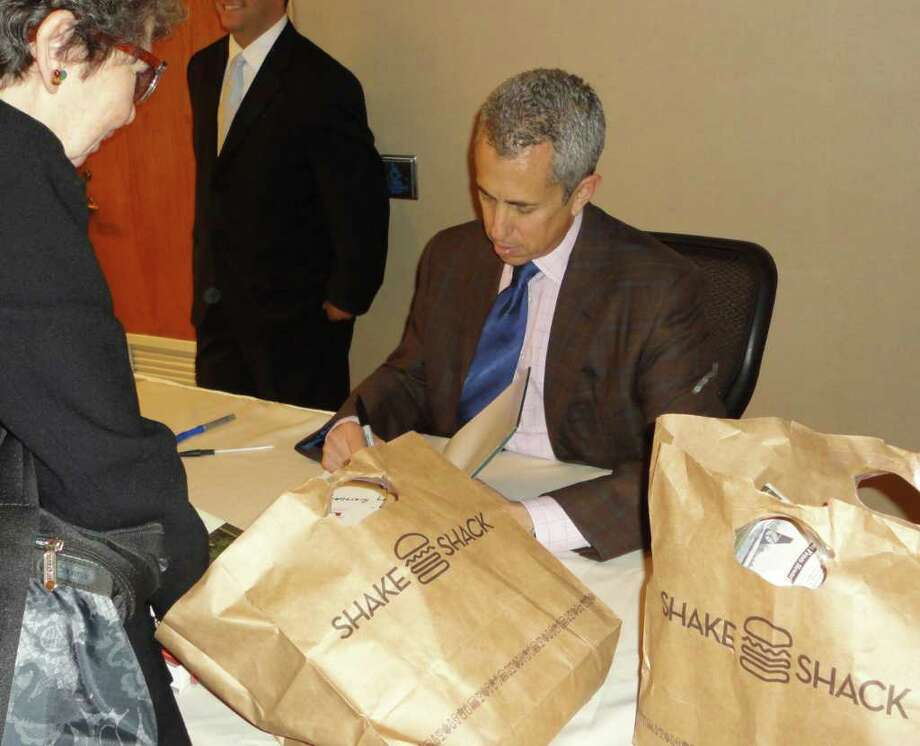 """As chef Danny Meyer autographed copies of his cookbooks and New York Times bestseller, """"Setting the Table,"""" on Wednesday at a Norwalk charity event, reminders of his Shake Shack restaurant chain, which has an outlet in Westport, were ubiquitous. Photo: Meg Barone / Westport News freelance"""