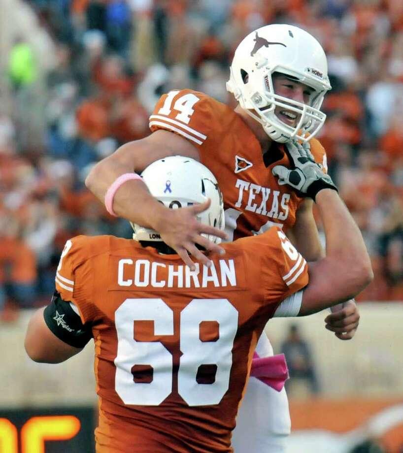 Texas quarterback David Ash, rear, celebrates his touchdown run against Kansas with Texas lineman Josh Cochran, front, in the first quarter during an NCAA college football game, Saturday, Oct. 29, 2011, in Austin, Texas. Photo: AP