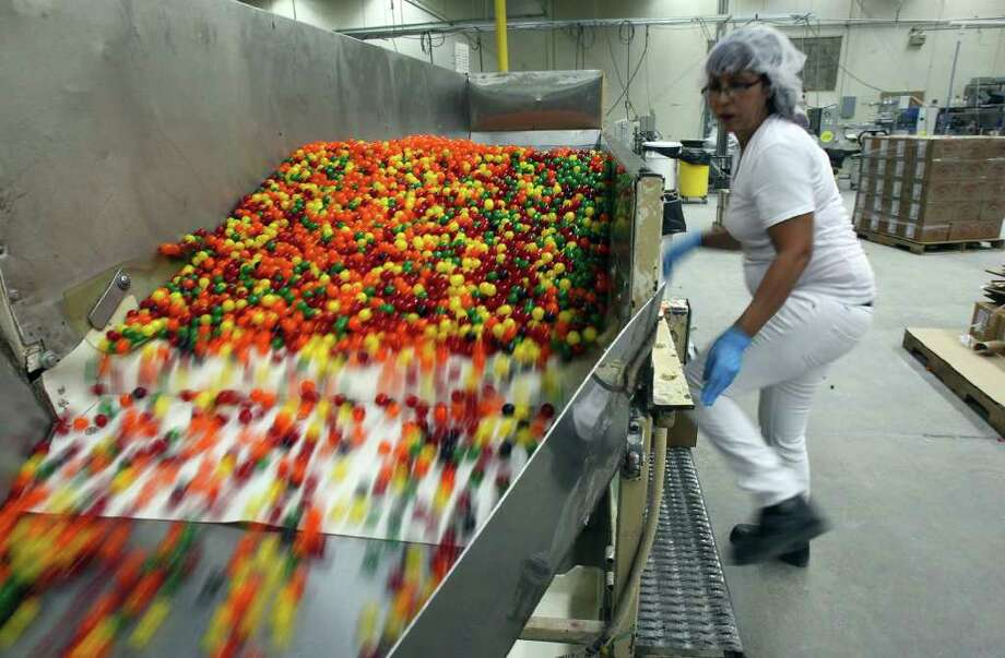 Dolores Pena prepares sour candies for packaging at Judson-Atkinson Candies on the East Side. On Tuesday, a small crew was packing the last of the sours before the company suspended production eight days earlier. Photo: JOHN DAVENPORT/jdavenport@express-news.net, SAN ANTONIO EXPRESS-NEWS