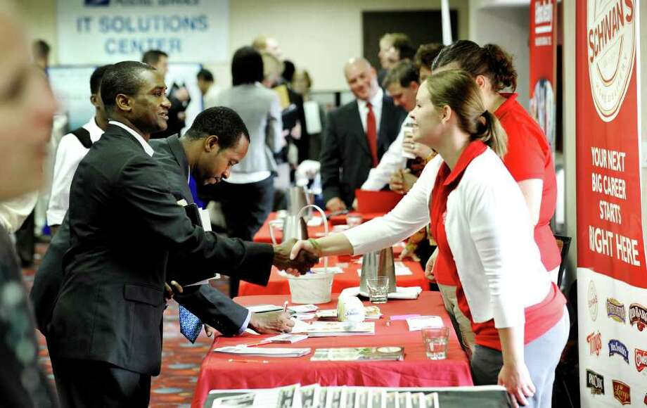 Job seekers visit the Minneapolis Career Fair held Wednesday, Nov. 2, 2011, in Bloomington, Minn. Fewer people applied for unemployment benefits last week, a positive sign that the job market is picking up a bit. (AP Photo/Jim Mone) Photo: Jim Mone
