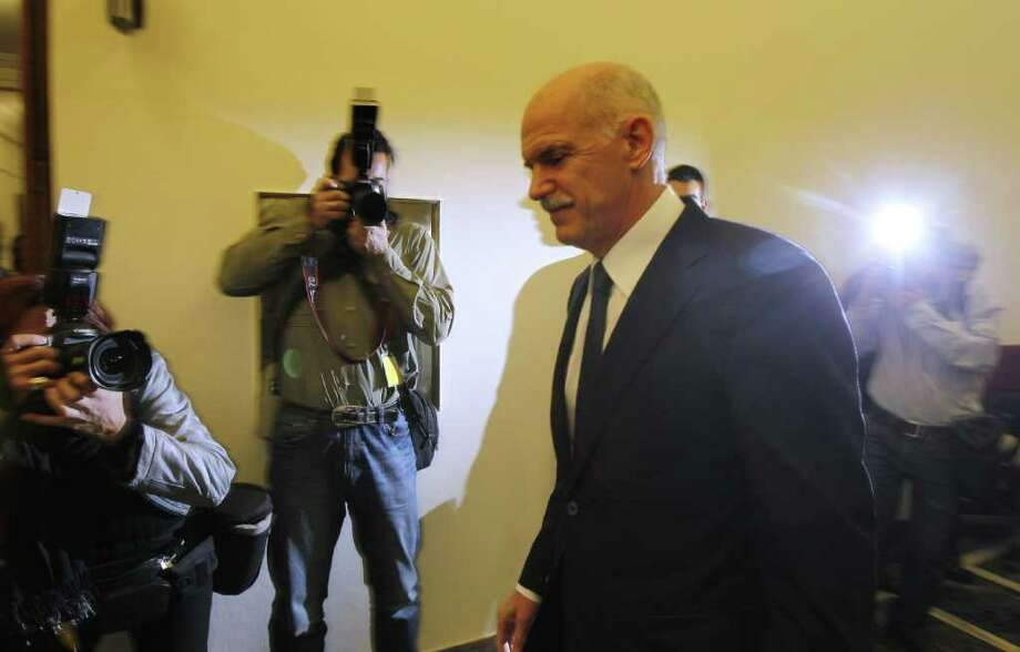 Greek Prime Minister George Papandreou returns to an emergency cabinet meeting after he took a short break at the Greek parliament in Athens, on Thursday, Nov. 3, 2011. A spokesman for Greece's government says it is prepared to discuss an opposition demand for the creation of a transitional government to approve the latest European bailout deal and secure the next installment of rescue loans for the country. (AP Photo/Thanassis Stavrakis) Photo: Thanassis Stavrakis / AP