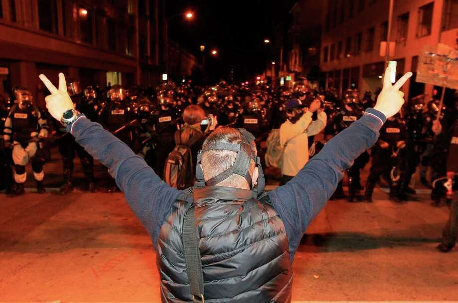 An Occupy protester shows peace signs to Oakland Police officers in Oakland, Calif., Thursday, Nov. 3, 2011. (AP Photo/Jeff Chiu) Photo: Jeff Chiu / AP