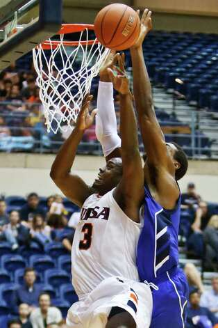 UTSA's Larry Wilkins (left) has a shot blocked by Texas A&M - Corpus Christi's Justin Reynolds during the Roadrunners 71-62 victory over the Islanders at the UTSA Convocation Center on Feb. 23 2011.  MARVIN PFEIFFER/mpfeiffer@express-news.net Photo: Express-News