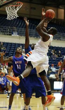 UTSA junior forward Larry Wilkins draws a foul from Aggie center Steph Colvin and Aggie guard Royce Robinson (11) looks on as UTSA men's basketball hosts Oklahoma Panhandle in a non-conference game Monday, January 24, 2011 at the Convocation Center at UTSA in San Antonio. ( Photo by J. Michael Short / SPECIAL ) Photo: J. Michael Short, Express-News / THE SAN ANTONIO EXPRESS-NEWS