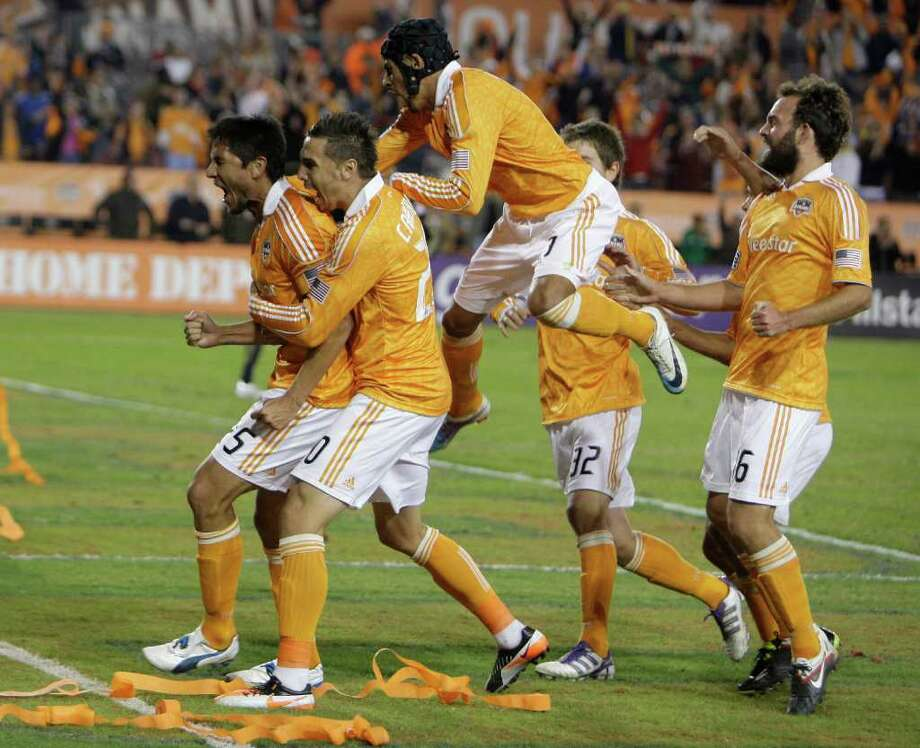 Houston Dynamo forward Brian Ching, left, celebrates with teammates after scoring a goal against the Philadelphia Union in the first half of a MLS playoff series game at Robertson Stadium, Thursday, Nov. 3, 2011, in Houston. Photo: Melissa Phillip, Houston Chronicle / © 2011 Houston Chronicle