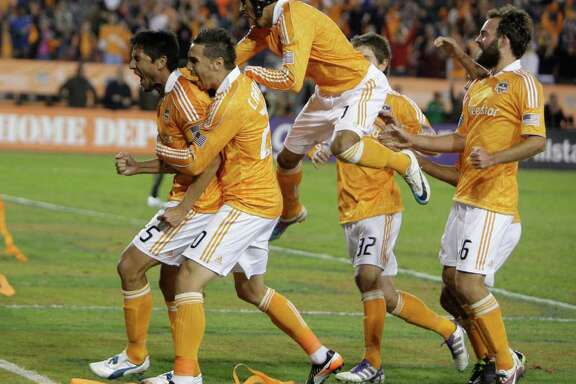 Houston Dynamo forward Brian Ching, left, celebrates with teammates after scoring a goal against the Philadelphia Union in the first half of a MLS playoff series game at Robertson Stadium, Thursday, Nov. 3, 2011, in Houston.