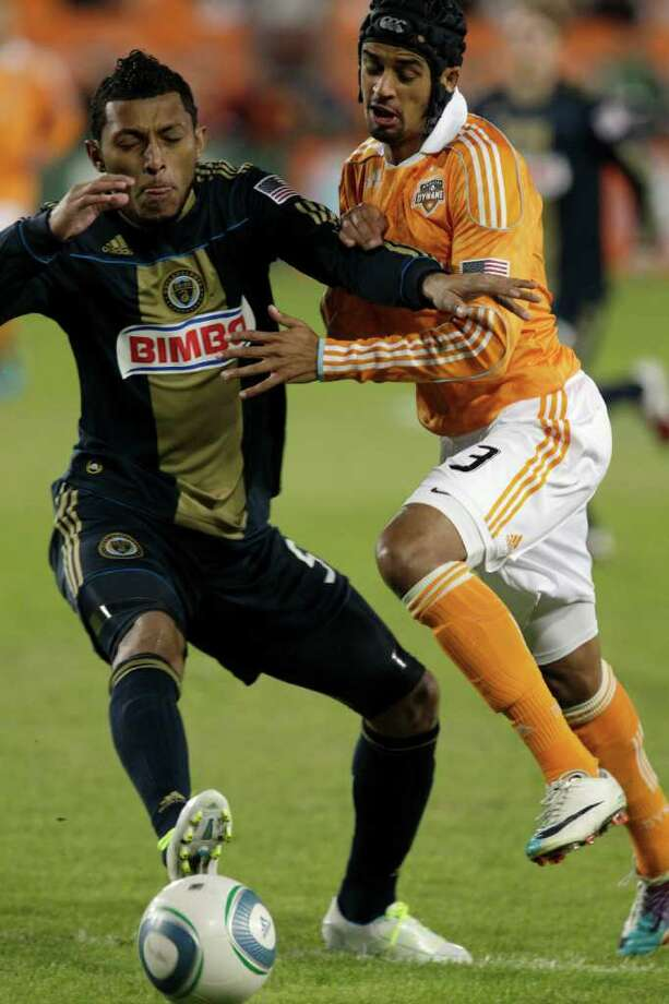Philadelphia Union defender Carlos Valdes, left, is challenged for the ball by Dynamo forward Calen Carr. Photo: Melissa Phillip, Associated Press / © 2011 Houston Chronicle