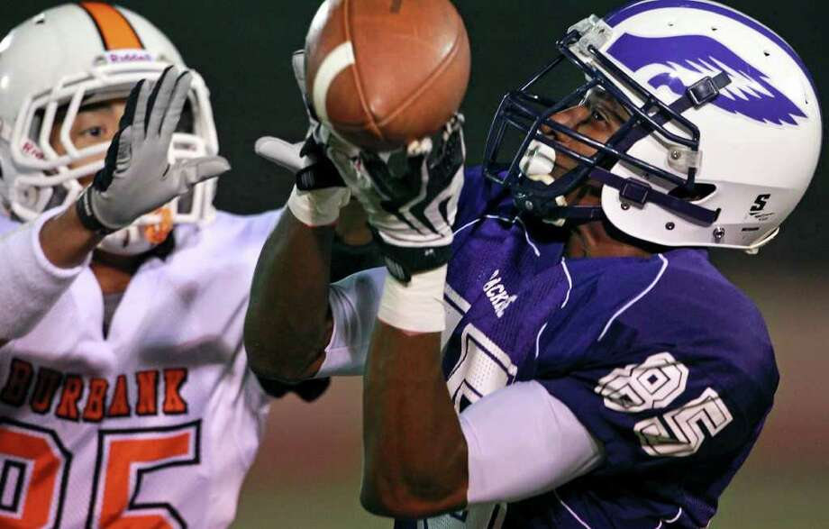 Eagle receiver Kenneth May burns the defense of Bull Dog  defender Carlos Reyes early in the first quarter by catching a long pass to set up a touchdown as Burbank plays Brackenridge at Alamo Stadium on  November 3, 2011.  Tom Reel/Staff Photo: TOM REEL, Express-News / © 2011 San Antonio Express-News