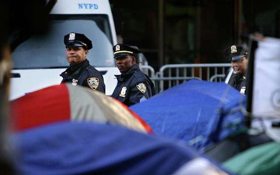 Police monitor the Occupy Wall Street protest encampment at Zuccotti Park on Thursday, Nov. 3, 2011. The protests, which started on Sept. 17 with a few dozen demonstrators who tried to pitch tents in front of the New York Stock Exchange, has grown into a nationwide and international movement. (AP Photo/Bebeto Matthews) Photo: Bebeto Matthews
