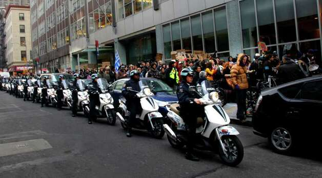 "Motorcycle police keep Occupy Wall Street protesters on the sidewalk as they  march to Goldman Sachs  headquarters on Thursday, Nov. 3, 2011 in New York.  A statement of a fraud verdict from a ""people's hearing"" held at Zuccotti Park, was read  out loud and handed over to Goldman Sachs officials.  (AP Photo/Bebeto Matthews) Photo: Bebeto Matthews"