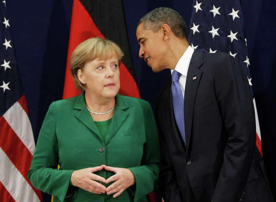 U.S. President Barack Obama, right, meets with German Chancellor Angela Merkel at the G20 Summit in Cannes, Thursday, Nov. 3, 2011. (AP Photo/Charles Dharapak) Photo: Charles Dharapak / AP