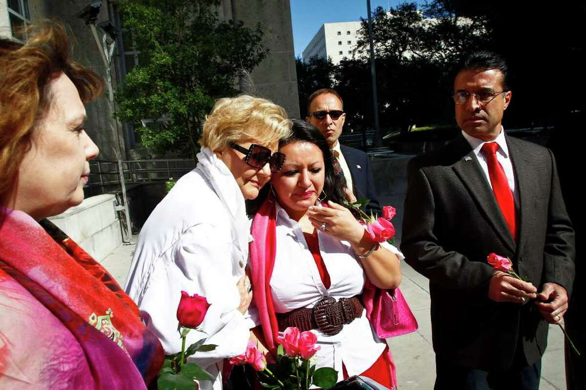 """Elizabeth Perez is comforted by Nancy Scott as Juda Myers and Fernando Herrera look on during a """"rape kit rally"""" on the steps of City Hall to urge Mayor Annise Parker to take action on the thousands of untested rape kits in the Houston Police Department's crime lab, Thursday, Nov. 3, 2011, in Houston."""