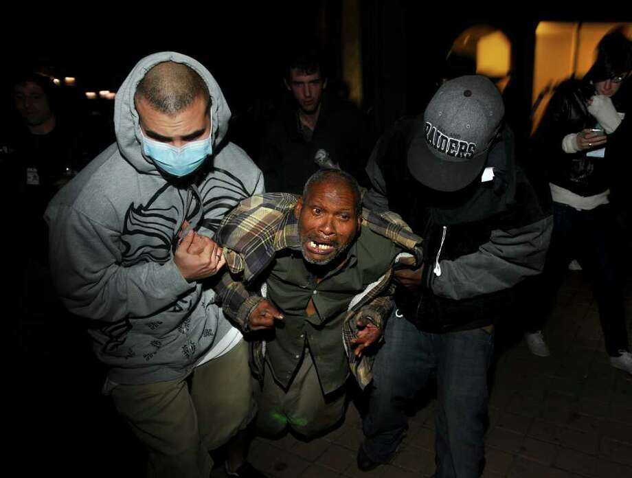 Protesters help an injured Occupy Oakland demonstrator after a police-fired projectile struck his leg on Thursday, Nov. 3, 2011, in Oakland, Calif. Following a mainly peaceful day-long protest by thousands of anti-Wall Street demonstrators, several hundred rallied through the night with some painting graffiti, breaking windows and setting file to garbage cans. (AP Photo/Noah Berger) Photo: Noah Berger