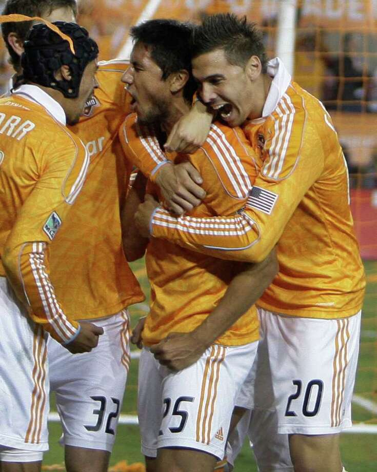 Melissa Phillip: Chronicle ONE TO REMEMBER: Dynamo forward Brian Ching, second from right, is surrounded by teammates Calen Carr, left, Bobby Boswell, rear, and Geoff Cameron, right, as they celebrate Ching's first-half goal. Photo: Melissa Phillip / © 2011 Houston Chronicle