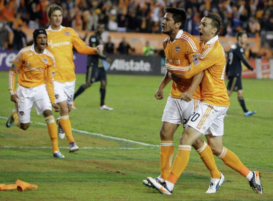 Houston Dynamo Brian Ching, left, is grabbed in celebration by teammate Geoff Cameron, right, after his goal against the Philadelphia Union in the first half of MLS playoff series at Robertson Stadium, Thursday, Nov. 3, 2011, in Houston. ( Melissa Phillip / Houston Chronicle ) Photo: Melissa Phillip / © 2011 Houston Chronicle