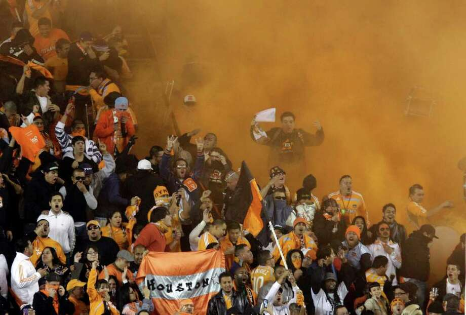 Houston Dynamo fans among orange-colored smoke set off in the stands during final minutes of game. Photo: Melissa Phillip / © 2011 Houston Chronicle