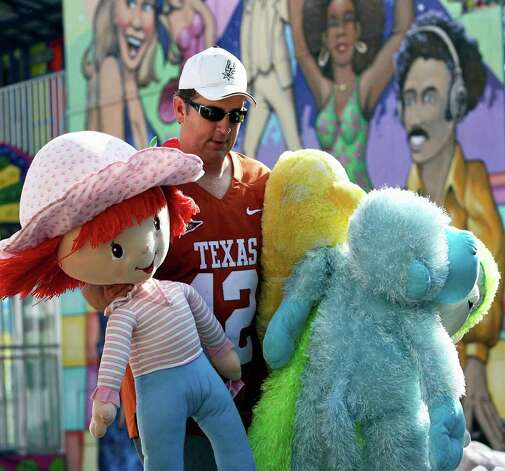 METRO   Paul Nemeth carries stuffed dolls which are prizes in his Make It Take It booth on the Wurstfest grounds where vendors are preparing for the first day of the yearly celebration.  Wurstfest runs from October 30 through November 8, 2009.  Tom Reel/Staff Photo: TOM REEL, SAN ANTONIO EXPRESS-NEWS / treel@express-news.net