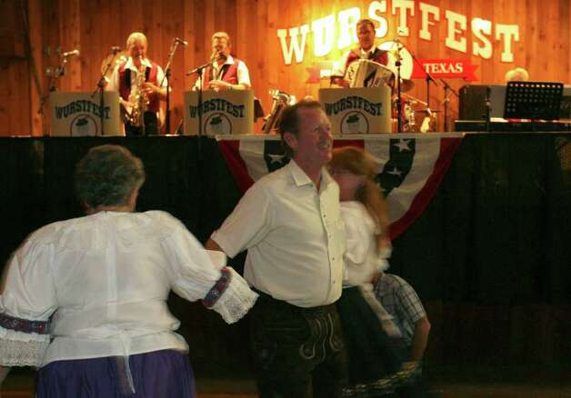 "David Smith of New Braunfels waltzes with Dorothy Warren (L) of Round Rock and Beth Warren of Austin at Wurstfest in New Braunfels Sunday. They were dancing to the the ""Garden Waltz."" Photo: JOHN DAVENPORT, SAN ANTONIO EXPRESS-NEWS / jdavenport@express-news.net"