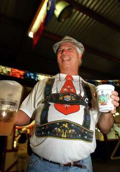 "Mike Stout, of Austin Texas, holds his pitcher of beer in one hand and mug in the other at Wurstfest in New Braunfels, Texas, Nov. 1, 2003. The city has been holding ""Wurstfest: The 10-day salute to sausage,"" for the last 46 years, drawing curious, and hungry, visitors from the world over. A large, lush park near a spring-fed river transforms every fall into the international center of Gemutlichkeit  ""fun and fellowship, German style.""  This year the event kicks off Nov. 2, 2007. (AP Photo/San Antonio Express-News, Bob Owen) ** ONLINES OK, MAGS OUT NO SALES ** Photo: BOB OWEN, AP / SAN ANTONIO EXPRESS-NEWS"