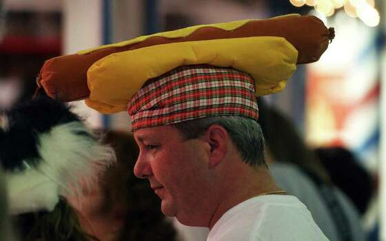 "METRO - Bruce Newton of Houston, Texas sports a ""hot dog"" hat at Wurstfest on Saturday, October 30, 2004. Wurstfest is a celebration of sausage coupled with Bavarian and Alpine entertainment. The event goes for 10 days. (Kin Man Hui/staff) Photo: KIN MAN HUI, SAN ANTONIO EXPRESS-NEWS / SAN ANTONIO EXPRESS-NEWS"