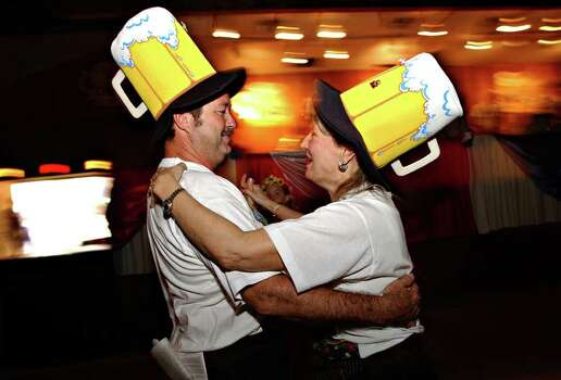 METRO DAILY - John Majewski, left, dances with his wife Kay wearing beer mug hats at Wurstfest in New Braunfels, Saturday, Nov. 1, 2003. The Majewskis are from Conroe, TX.  photo Bob Owen Photo: BOB OWEN, SAN ANTONIO EXPRESS-NEWS / SAN ANTONIO EXPRESS-NEWS