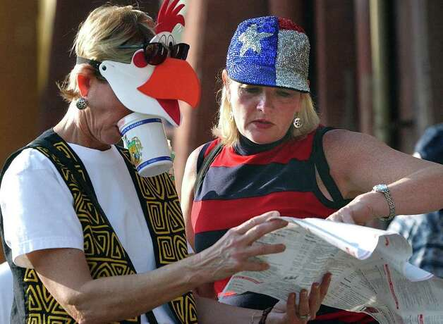 Metro  Jackie Mitchell of New Braunfels (left) juggles her beer cup while checking a Wurstfest map with her friend Jo Fisher of Dallas  Saturday afternoon.  Photo by Tom Reel  November 10 Photo: TOM REEL , EN / EN