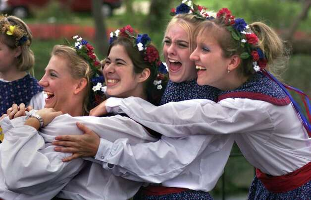 Dressed in traditional German outfits , four girls from  the El Campo High School German Dance  group, share some fun before a group picture at Wurstfest Saturday afternoon, November 4.  Left to right are Katie Little, Lindsey Schmidt, Amber Pfeffer, and Heather Ladewig.  All are seniors at the high school.   Photo by Tom Reel Photo: TOM REEL