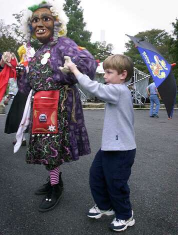 "Christopher Hicks, 6, takes a whirl with a dancing character from ""Heritagefest Narren"" Saturday at the entrance to Wurstfest in New Braunfels.  The masked group, the origainal wooden mask group performing in the U.S>, is from New Ulm , Minnesota and is making it's second appearance at the event. Photo: TOM REEL"