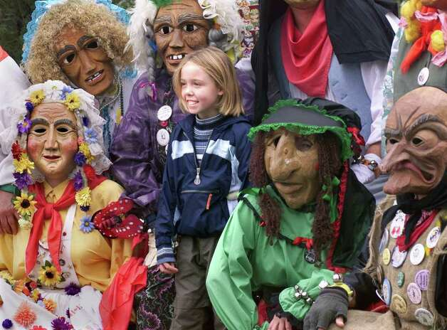 SUNS  Eight year old Alexis Todd is surrounded by characters from the wooden mask group  Heritagefest Narren as she visits Wurstfest Saturday, November 4 with her grandmother who snapped a picture of the girl in this scene.    Photo by Tom Reel Photo: TOM REEL