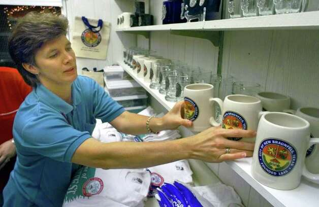 Metro  Laura Stolinski sets out mugs at the City Store, the City of New Braunfels booth, at the Wurstfest grounds Thursday, October 28.  The annual celebration begins Friday evening. Photo: TOM REEL