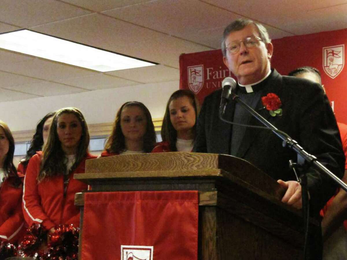 Fairfield University President Rev. Jeffrey P. von Arx, S.J., speaks at a press conference Friday that preceded a ribbon-cutting for the Fairfield University Bookstore at 1499 Post Road. Behind him are members of the university's dance squad.