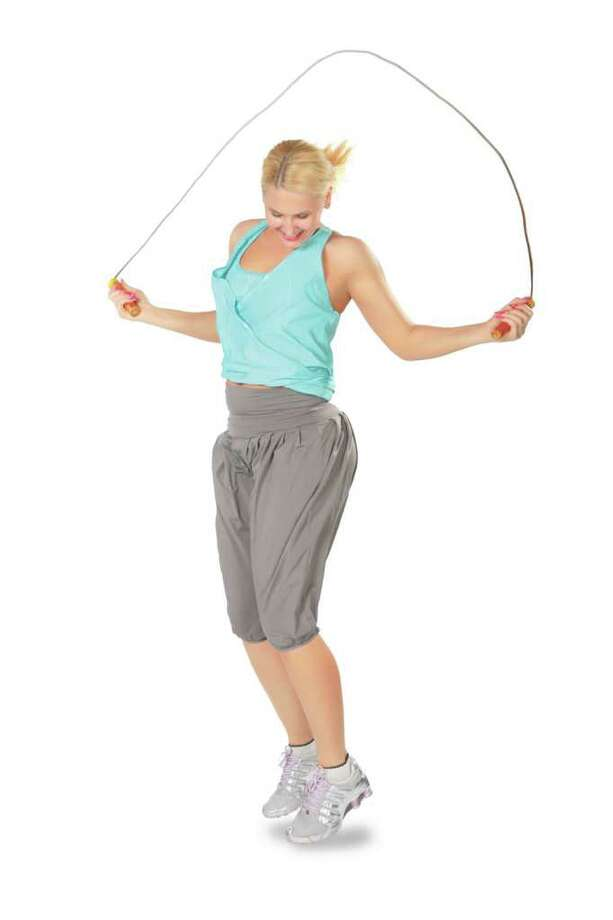 Woman jumps with a skipping rope / Pavel Losevsky - Fotolia