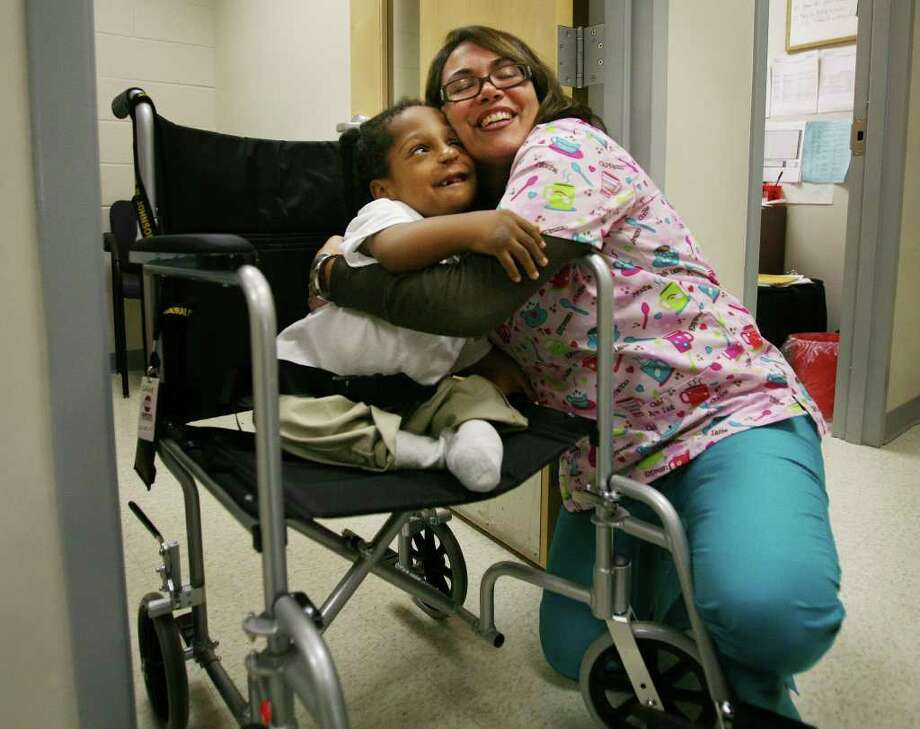 First grader Charlie DeLoSantos, 6, gives a big hug to school nurse Carrie Cotto, RN, at Geraldine W. Johnson School in Bridgeport, Conn. Cotto said she enjoys getting to know her patients, and that she treats each one as if they were her own children. Photo: Brian A. Pounds / Connecticut Post