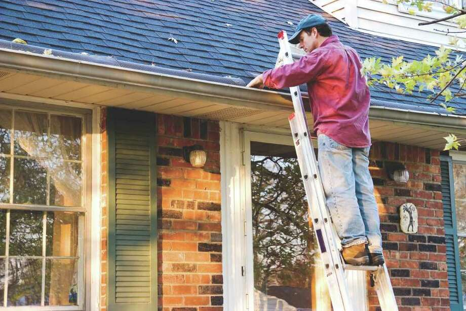 Man cleaning gutters on ladder / gmcgill - Fotolia