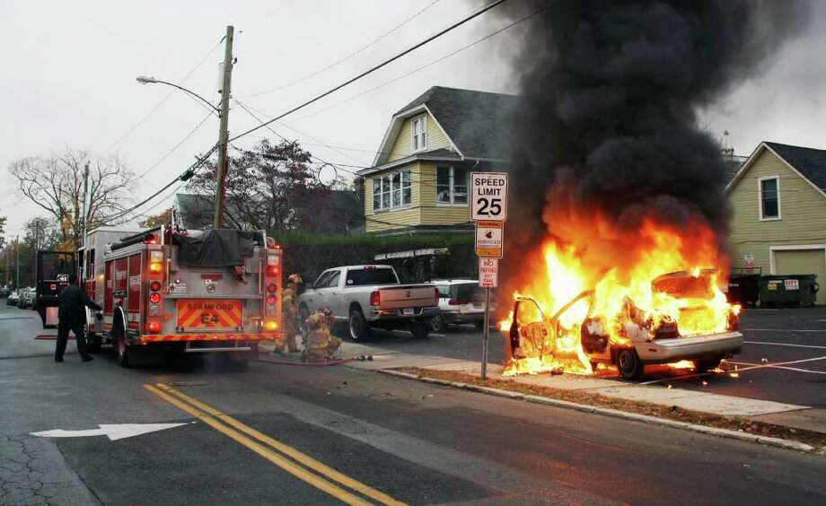 Stamford Fire & Rescue Department firefighters work to extinguish a car fire at the intersection of Waterbury Avenue and East Main Street Friday morning. Photo: Contributed Photo