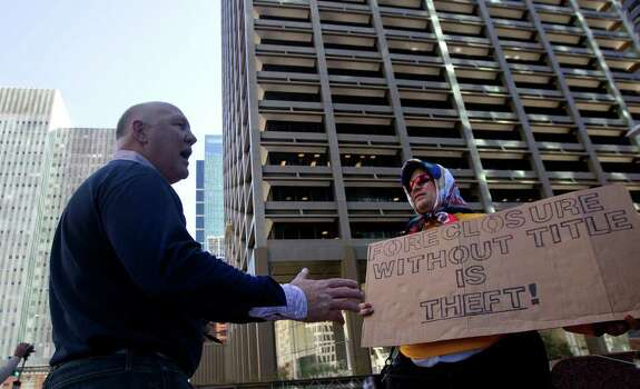 Marty Power,left, argues with Occupy Houston protestor Benjamin Franklin, right, outside of Wells Fargo Plaza Friday, Nov. 4, 2011, in Houston. Protestors made a Divestment March where they protested outside four nearby banking institutions in downtown Houston - Bank of America, JP Morgan Chase, Wells Fargo and Amegy. (Cody Duty / Houston Chronicle) Photo: Cody Duty / © 2011 Houston Chronicle