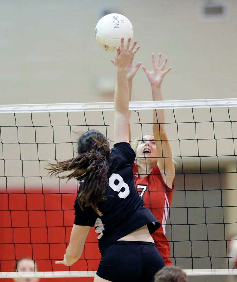 Andrea Mullaney, # 9 of New Canaan High School spikes one past Liza Johnson, # 7 of Greenwich during FCIAC girls volleyball match between Greenwich High School and New Canaan High School at New Canaan High School, Thursday afternoon, Nov. 3, 2011. Photo: Bob Luckey / Greenwich Time