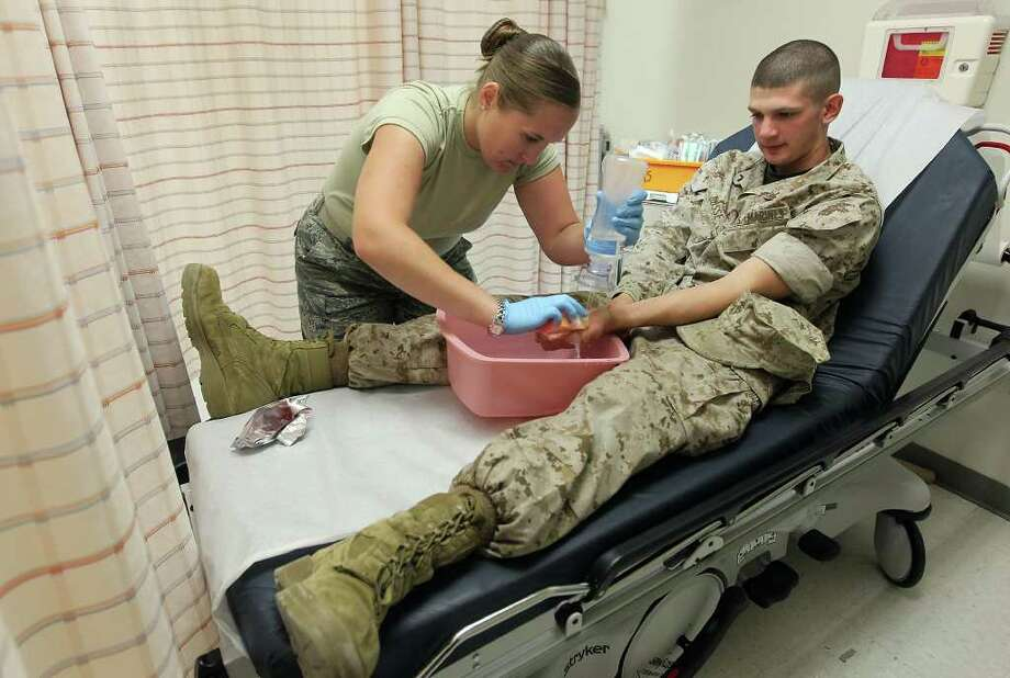 Army Staff Sgt. Leigh Jones irrigates a cut on the thumb of Marine Pfc. Jared Busse at Wilford Hall's Urgent Care facility on Wednesday, Nov. 2, 2011. Since July, Wilford Hall has transitioned from a Trauma Level One emergency hospital into the urgent care only facility. Hospital officials are urging people who have life-threatening conditions like heart attacks to seek out the current level one hospitals such as University Hospital or San Antonio Military Medical Center for their emergency health needs. Wilford Hall treats military, retired military and their dependents.  Kin Man Hui/kmhui@express-news.net Photo: Kin Man Hui, SAN ANTONIO EXPRESS-NEWS / San Antonio Express-News