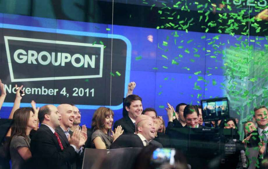 Employees and guests of Groupon, celebrate the company's IPO at Nasdaq, Friday, Nov. 4, 2011 in New York. CEO Andrew Mason is center rear. Groupon, the company that pioneered online group discounts, has begun trading as a public company. The stock jumped nearly 50 percent in the opening minutes Friday. (AP Photo/Mark Lennihan) Photo: Mark Lennihan, ASSOCIATED PRESS / AP2011