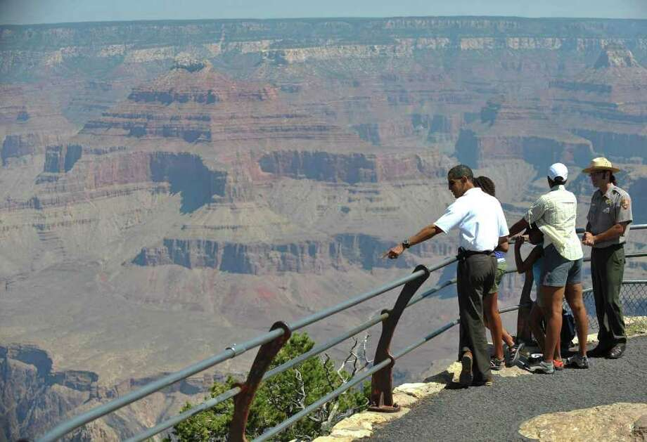 MANDEL NGAN : AFP/GETTY IMAGES A GRAND VIEW: President Barack Obama, Michelle Obama and their daughters Sasha and Malia tour Hopi Point at the Grand Canyon National Park with Park Ranger Scott Kraynak in 2009. Photo: MANDEL NGAN / AFP