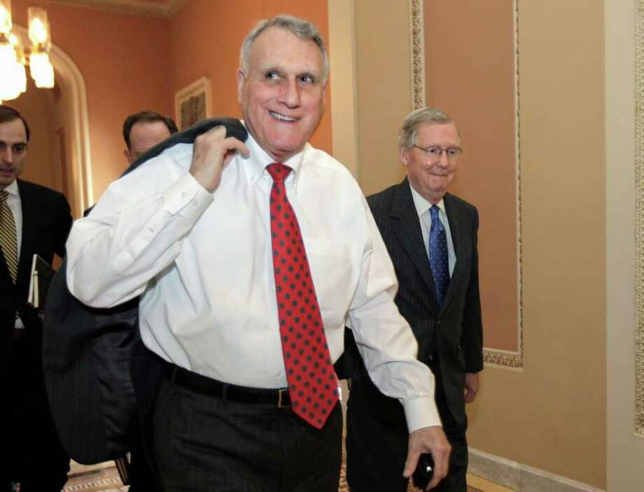 Senate Minority Whip Jon Kyl of Ariz., left, Senate Minority Leader Mitch McConnell of Ky., right, and others, walk to the floor of the Senate on Capitol Hill in Washington, Thursday, Nov. 3, 2011, to deliver a defeat to Democrats and President Obama on the stimulus-style jobs agenda, blocking a $60 billion measure for building and repairing infrastructure like roads and rail lines. (AP Photo/J. Scott Applewhite) Photo: J. Scott Applewhite / AP