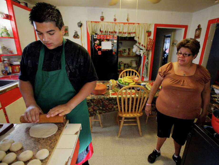 Velma Cantu, right, teaches her grandson, Isidro Zarate, 14, how to make tortillas, Tuesday, Oct. 25, 2011, at her home in San Antonio. Photo: Darren Abate, Darren Abate/Special To The Express-News
