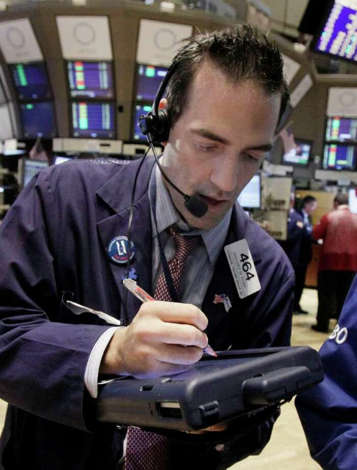 In this Nov. 3, 2011 photo, trader Gregory Rowe, right, works on the floor of the New York Stock Exchange. World stock markets rose Friday, Nov. 4, 2011, amid relief Greece's prime minister had abandoned a referendum on the country's bailout but gains in Europe were muted ahead of monthly U.S. employment figures. (AP Photo/Richard Drew) Photo: Richard Drew